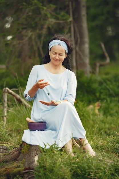 Старшая женщина с индуистскими вещами. дама в голубом платье. брюнетка сидит. Бесплатные Фотографии