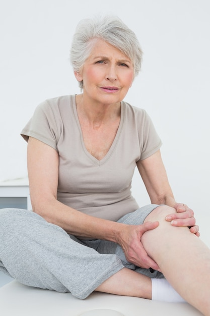 Senior woman with painful knee sitting on examination table Premium Photo