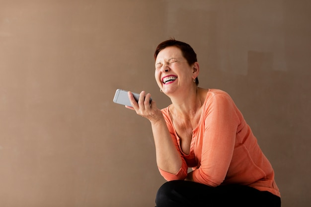 Senior woman with phone having a good time Free Photo
