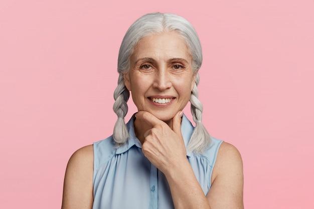 Старшая женщина с косичками, одетая в синюю блузку Бесплатные Фотографии