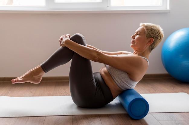 Senior woman with short hair using a yoga mat Free Photo