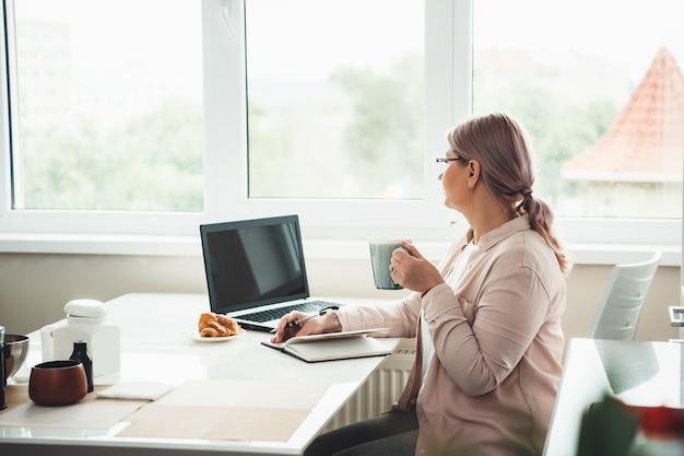 クロワッサンでお茶を飲みながら窓を見ながら検疫中に自宅で仕事をし、コンピューターで働く年配の女性 Premium写真