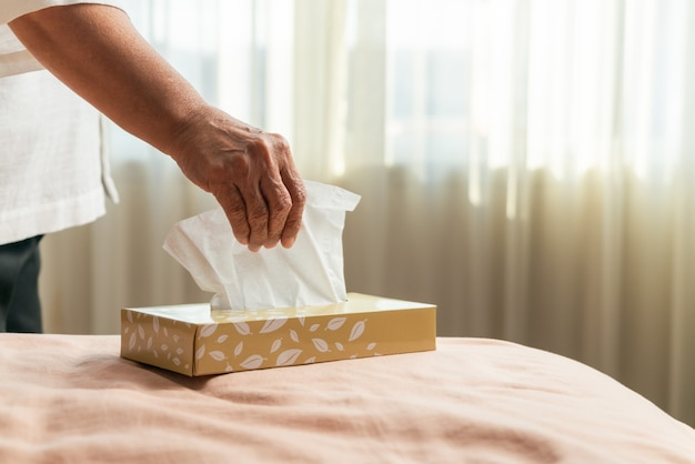 Senior women hand picking napkin/tissue paper from the tissue box Premium Photo