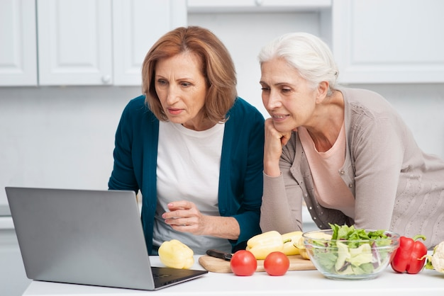 Senior women looking for cooking recipies Free Photo