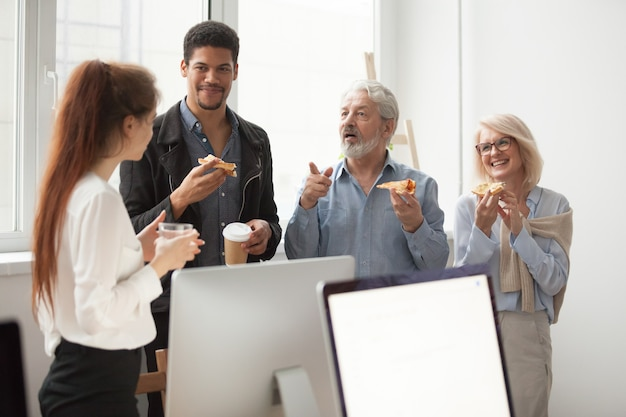 Senior and young colleagues talking while eating pizza in office Free Photo