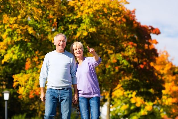 Seniors in autumn or fall walking hand in hand Premium Photo