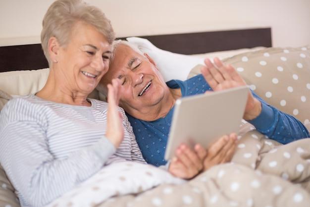 Anziani che hanno una videoconferenza gioiosa Foto Gratuite