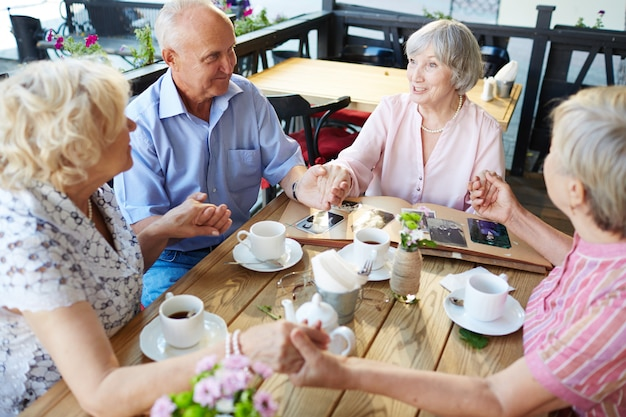 Seniors holding hands in cafe Free Photo
