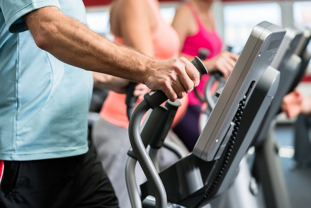 Seniors train on cross trainer with personal trainer at the gym Premium Photo
