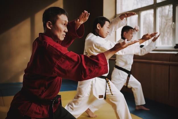 Сэнсэй и два студента боевых искусств занимаются вместе. Premium Фотографии