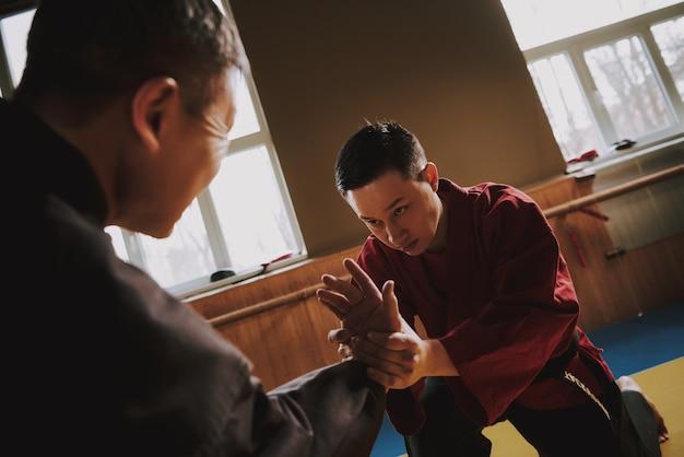 Premium Photo Sensei In Black Teaching Martial Arts Student