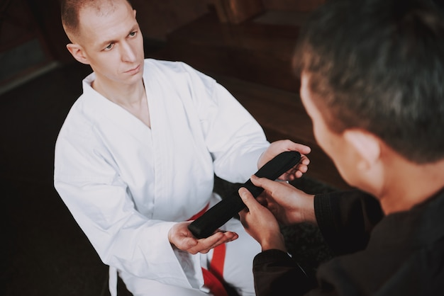Sensei is giving black belt to martial arts fighter Premium Photo