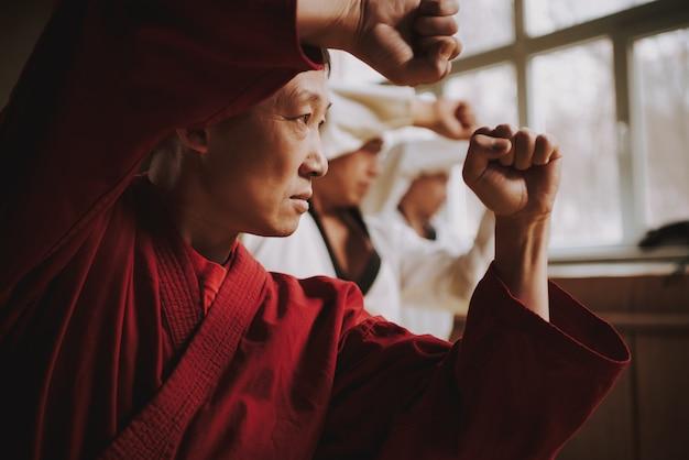 Sensei in red two martial arts students training Premium Photo