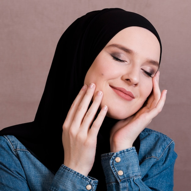 Sensual arabian woman touching her cheeks against colored surface Free Photo