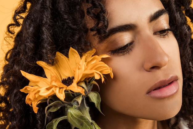 Sensual ethnic pensive woman with flower Free Photo