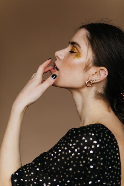 官能的なヨーロッパのモデルは、茶色の壁に立っている金色のアクセサリーを身に着けています。きらめくパーティーメイクで魅力的な黒髪の女性の屋内写真。 無料写真