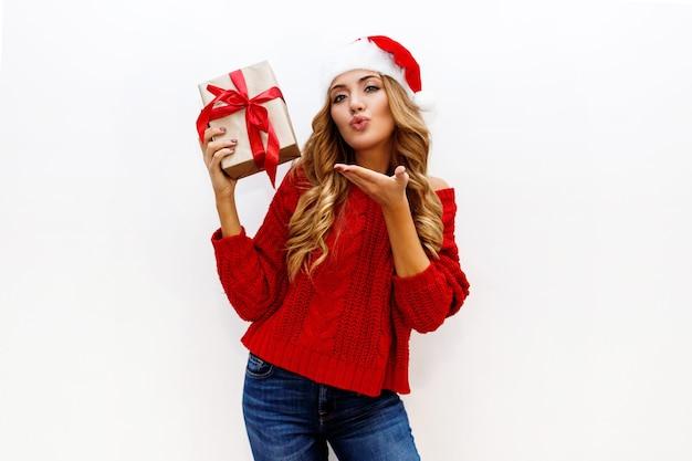 빛나는 금발 물결 모양의 머리카락을 가진 관능적 인 소녀가 키스를 보냅니다. 패션 겨울 모습. 새해 복장. 에어 키스를 보냅니다. 무료 사진