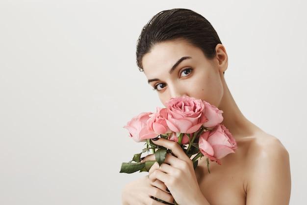 Ragazza sensuale che sente l'odore del mazzo di rose mentre si trovava nuda sul grigio Foto Gratuite