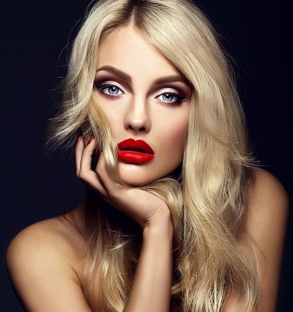 Sensual glamour portrait of beautiful blond woman model lady with bright makeup and red lips touching her face , with healthy curly hair on black background Free Photo