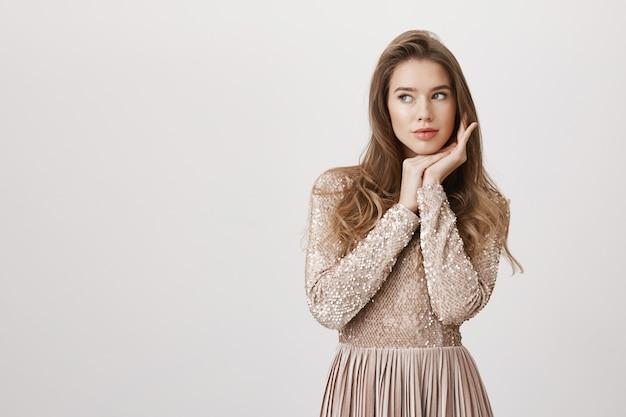Чувственная гламурная женщина в блестящем платье смотрит налево Бесплатные Фотографии