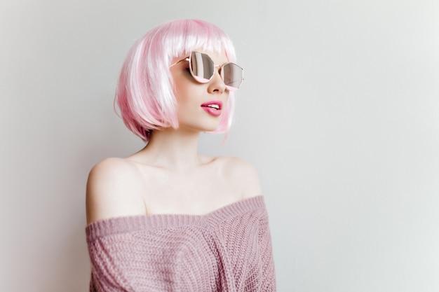 明るい壁にポーズをとるピンクのかつらの官能的な素敵な女の子。立っているニット紫の服装できれいな女性の屋内肖像画 無料写真