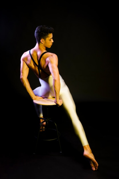 Sensual male ballet dancer sitting in spotlight Free Photo