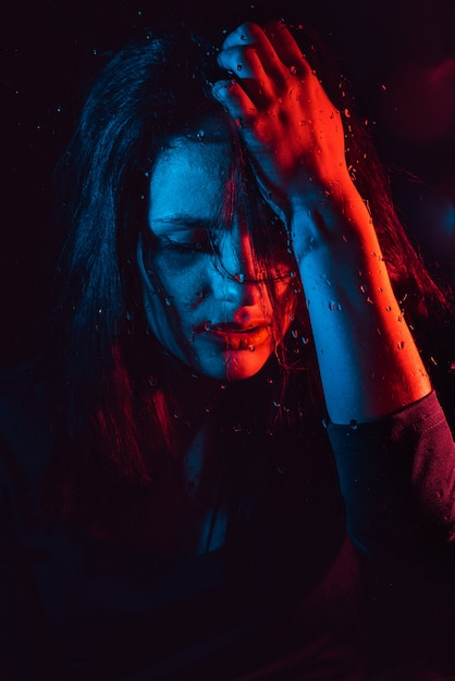 Sensual portrait of beautiful girl behind glass with raindrops with red blue lighting Premium Photo