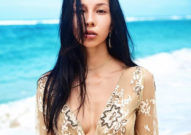 Чувственный портрет красивой кавказской модели женщины с темными длинными волосами в бежевой блузке, позирующей на летнем пляже с белым песком на фоне голубого неба и океана Бесплатные Фотографии