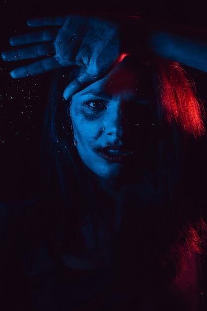 Sensual portrait of sad melancholic lonely girl behind glass with raindrops Premium Photo