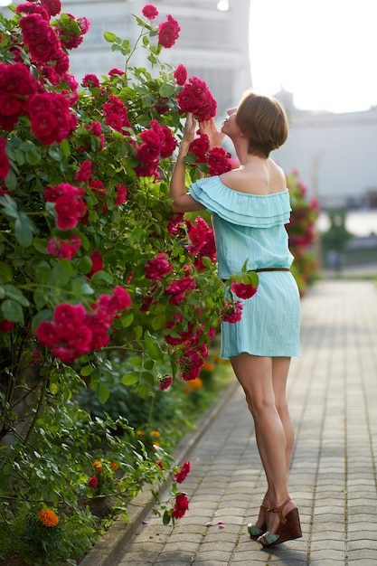 Sensual redhead girl wearing stylish blue light dress smelling blooming roses in the garden. outdoor. Premium Photo