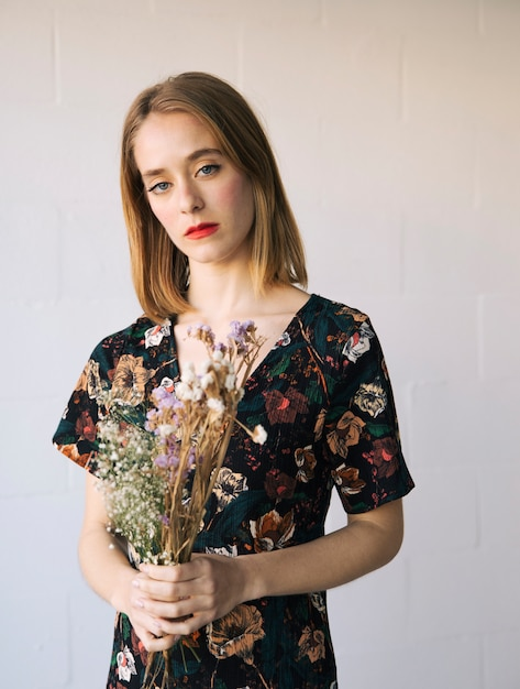 Sensual sad woman with bouquet of dry plants Free Photo