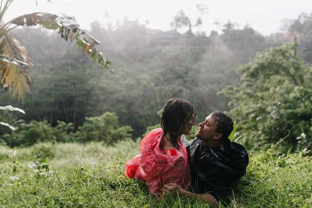 Чувственная женщина в плаще позирует на траве с парнем. пара путешественников смотрят друг на друга во время отдыха после похода. Бесплатные Фотографии