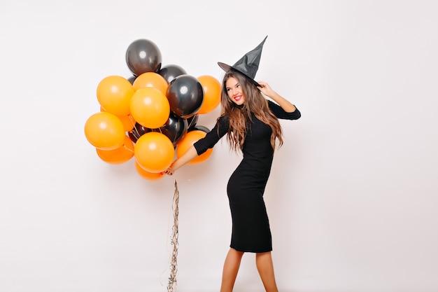 Чувственная женщина в костюме ведьмы ждет хэллоуина и держит оранжевые воздушные шары Бесплатные Фотографии