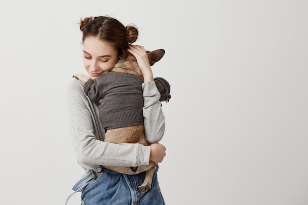 Чувственная женщина с детской прической, являющейся мамой щенка, в то время как это лежало на ее плече со спиной. чувство заботы и любви, выраженное владельцем женского пола. Бесплатные Фотографии