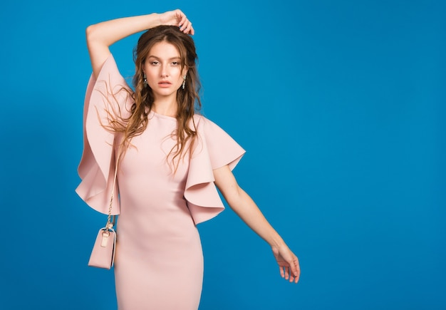 핑크 럭셔리 드레스, 여름 패션 트렌드, 세련된 스타일, 블루 스튜디오 배경, 유행 핸드백을 들고 관능적 인 젊은 세련된 섹시한 여자 무료 사진