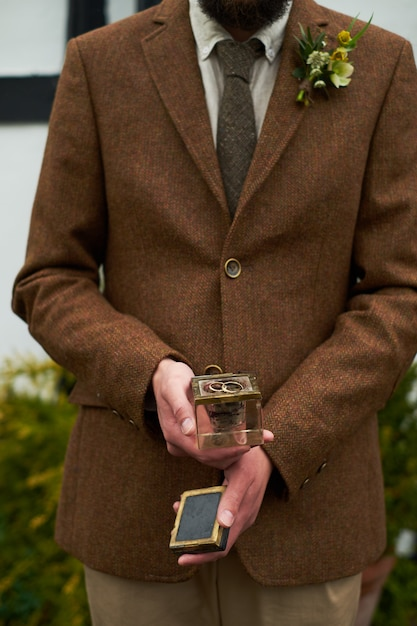Sentence. hands of a man in a brown jacket holding a glass gift box with a ring. Premium Photo