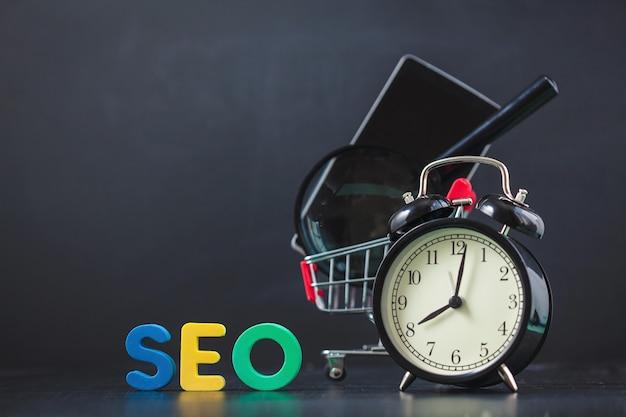 Цветные буквы seo с часами, увеличительное стекло, смартфон, шестерни в корзине на черном фоне копия пространство Premium Фотографии