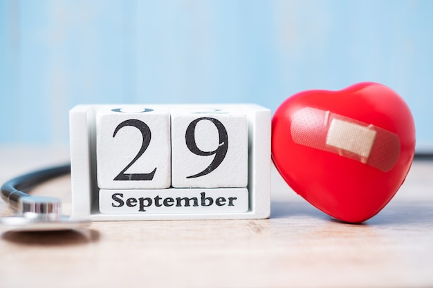 September 29 of white calendar and stethoscope with red heart shape Premium Photo