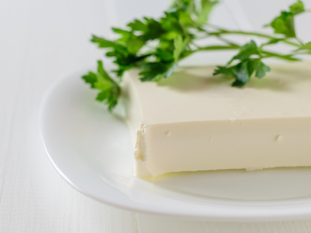 Serbian cheese with parsley leaves on a white table on a white background. Premium Photo