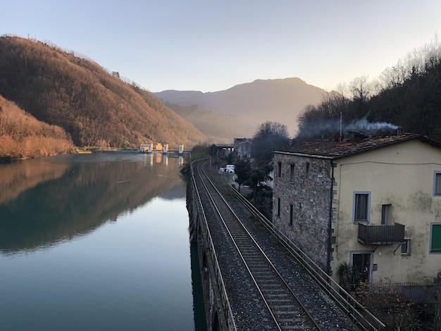 Озеро серкио, окруженное железной дорогой, зданиями и холмами, покрытыми лесами в италии Бесплатные Фотографии