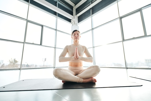 Serene girl in activewear sitting in pose of lotus on mat during relaxation exercise Premium Photo