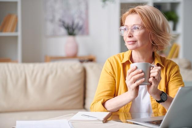 パンデミック期間中に自宅でラップトップの前でリモートで作業しながら熱いお茶やコーヒーを飲んでいる短いブロンドの髪を持つ穏やかな成熟した女性 Premium写真