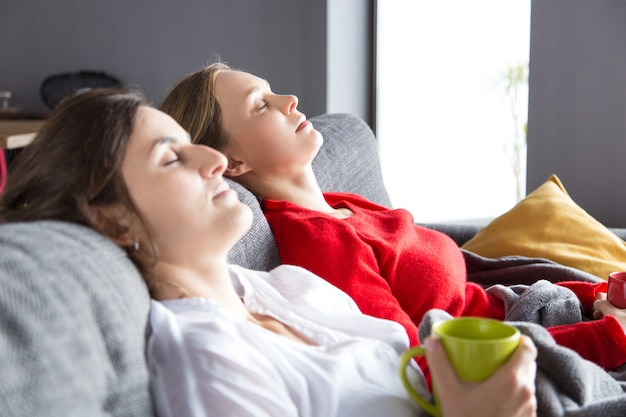Serene roommates resting on couch over cup of tea Free Photo
