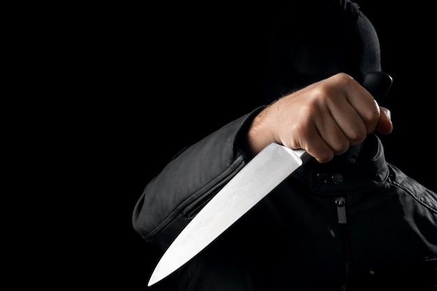 The serial killer, a maniac with a knife and a black chuolkom on his head Premium Photo