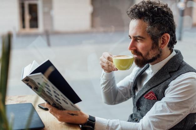 Серьезный взрослый мужчина средних лет пьет и наслаждается кофейным напитком, читая интересную и увлекательную книгу в кафе или библиотеке. Бесплатные Фотографии