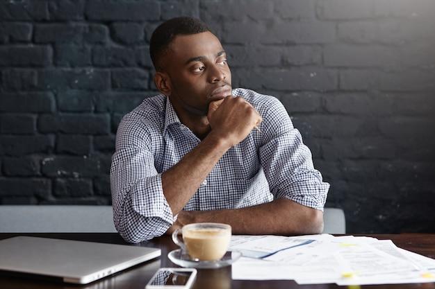 Uomo d'affari afroamericano serio che mangia caffè al caffè Foto Gratuite