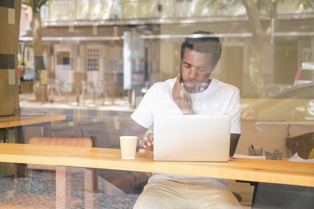 노트북에 입력하고 공동 작업 공간에서 휴대폰에 말하기 심각한 아프리카 계 미국인 남자 무료 사진