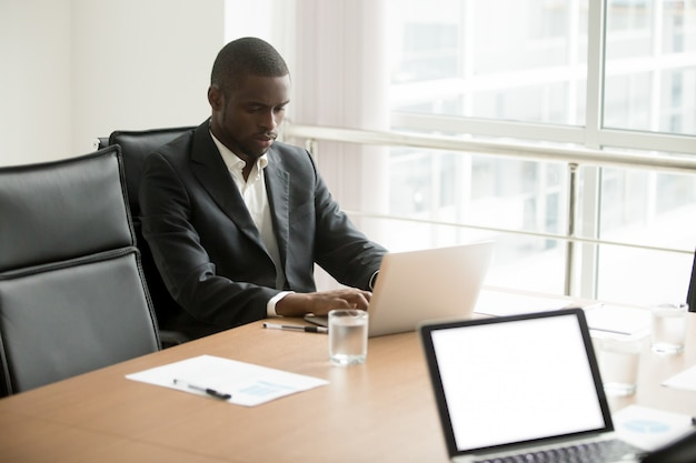 Serious african businessman working on laptop sitting at conference table Free Photo