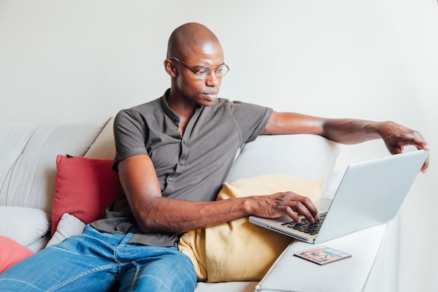 Serious african young man sitting on sofa using laptop at home Free Photo