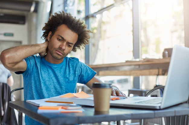 Serious afro american male student in blue t-shirt sitting at cafeteria drinking takeaway coffee working at his project using books and laptop touching his neck with hand having pain Free Photo